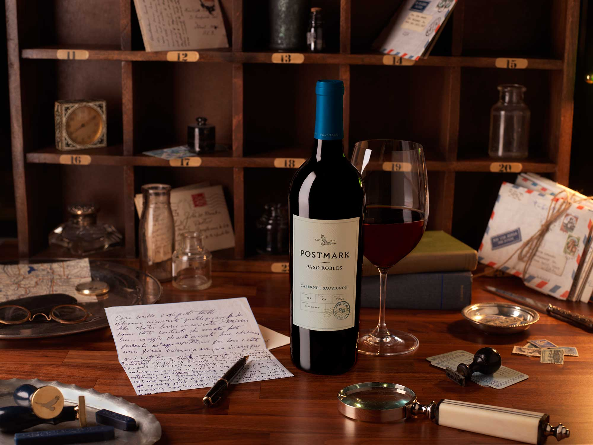 Postmark Wine Bottle and Glass of Paso Cabernet Sauvignon on Desk