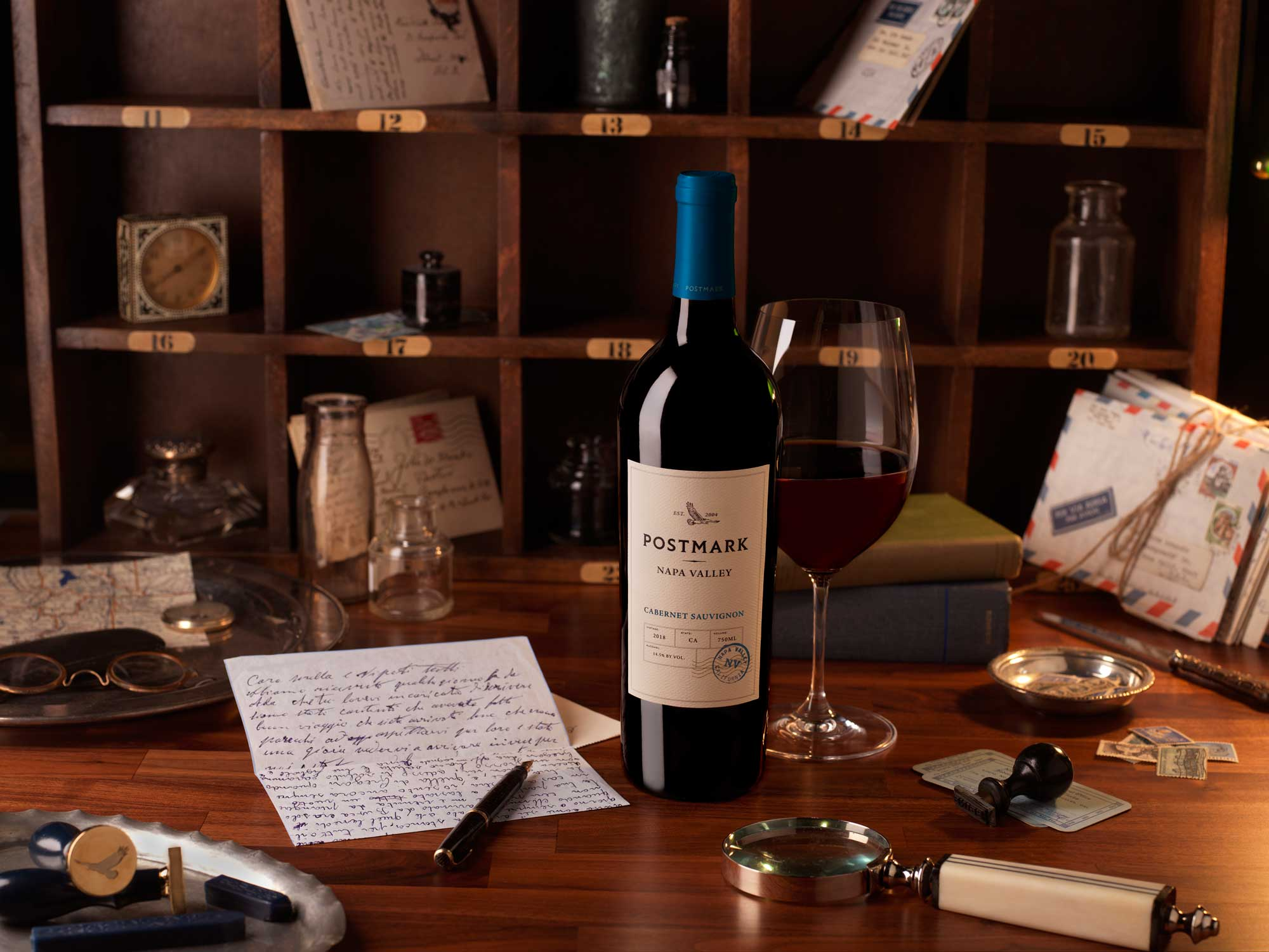 Postmark Wine Bottle and Glass of Napa Cabernet Sauvignon on Desk